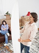 Man with surf board in home with boxes and woman on sofa