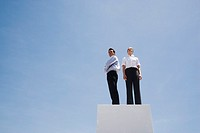 Businessman and woman standing on pedestal outdoors with blue sky