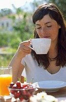 Young woman drinking tea at the breakfast table
