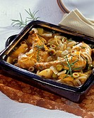 Chicken legs on a bed of potatoes and olive