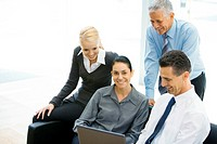 Business associates looking at laptop together, woman in center smiling at camera
