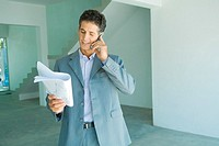 Well-dressed man looking at blueprints, using phone