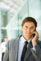Young businessman using cell phone, looking away, portrait