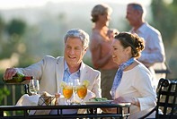 Mature couple dining at outdoor restaurant table, man pouring glass of wine, smiling, second couple talking in background differential focus