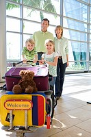Family standing beside luggage trolley in airport, smiling, front view, portrait, soft toy on suitcase