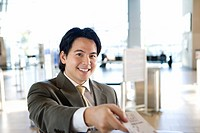 Businessman checking in at airport, receiving boarding pass from check-in attendant, smiling, portrait, view from behind check-in desk differential fo...