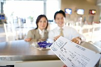 Business couple checking in at airport, focus on boarding passes in check-in attendantÔÇÖs hands in foreground, view from behind check-in desk