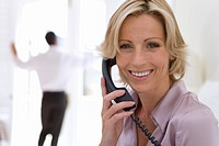Businesswoman using telephone, smiling, portrait, man standing in background