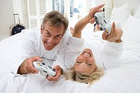 Mature couple playing computer game on bed, smiling, portrait
