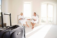 Mature couple wearing white bath robes, sitting and holding hands, suitcase in foreground