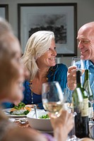 Mature couple smiling at each other at dinner table, mature woman smiling in foreground