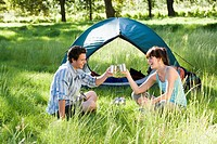 Young couple sitting near dome tent on camping trip in woodland clearing, making celebratory toast with mugs