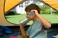 Boy 8-10 sitting on sleeping bag inside tent on garden lawn, playing with tin can phone, profile