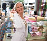 Mature woman in clothing store, holding shirt, smiling, portrait