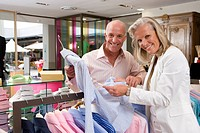 Mature couple in clothing store, holding shirt, smiling, portrait