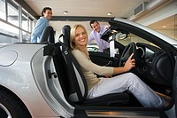 Car salesman showing couple new silver convertible in large car showroom, focus on woman sitting in driving seat in foreground, smiling, side view, po...