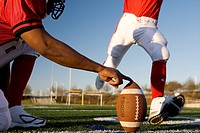 American football player attempting to kick field goal, teammate holding ball vertically against pitch surface level