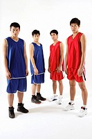 Young men in basketball uniforms looking at camera