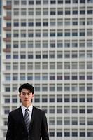 Businessman looking at camera, building behind him