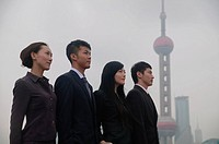 Business people standing in a row, looking away, Oriental Pearl TV Tower in the background