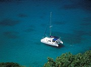 Man swimming in the sea beside his catamaran yacht off Pigeon Island, Rodney Bay, St  Lucia