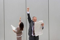 Businesspeople holding newspaper