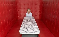 Businesswoman working at a table with red seating