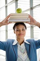 African businesswoman with books on head