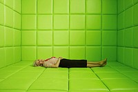 Woman resting in green padded cell