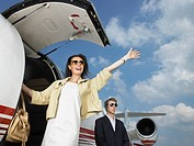 Smiling woman exiting private jet with bodyguard