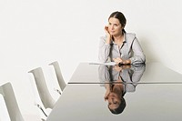 Young business woman at desk with reflections