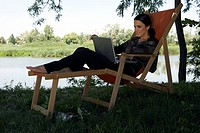 Woman on deckchair with laptop by river