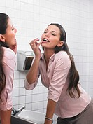 Woman reflected in office washroom mirror applying make-up
