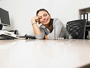Businesswomen sitting at her desk with a Newton´s Cradle