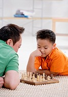 Father and son at home, playing chess