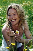 Woman is sitting in a meadow and is playing with a flower