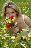 Woman is sitting in a meadow with a bunch of flowers