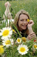 Woman is lying on a meadow and holding a flower