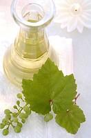 Traubenkernöl aus wießen Trauben in einer Karaffe mit Kerze und Traubenblatt