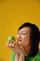 Young Woman holding apple, eyes closed