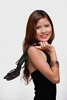Woman holding high heeled shoes over shoulder