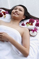 Young woman lying down on massage table, looking up