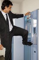 Businessman hitting a vending machine with his leg