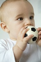 Baby putting toy soccer ball in mouth, close-up