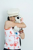 Teenage girl embracing stuffed toy, smiling at camera, portrait