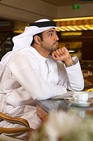 Side View of Arab Business Man Reading Newspaper with cappuccino at Café  Dubai, United Arab Emirates