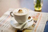 Cappuccino sitting on Arab newspaper in cafe  United Arab Emirates
