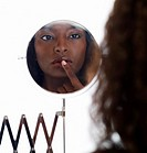 Woman Looking in a Mirror Touching her Finger to her Lips  Studio Shot