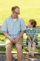 Father and son sitting on park bench