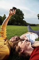 Boys lying in field taking photos